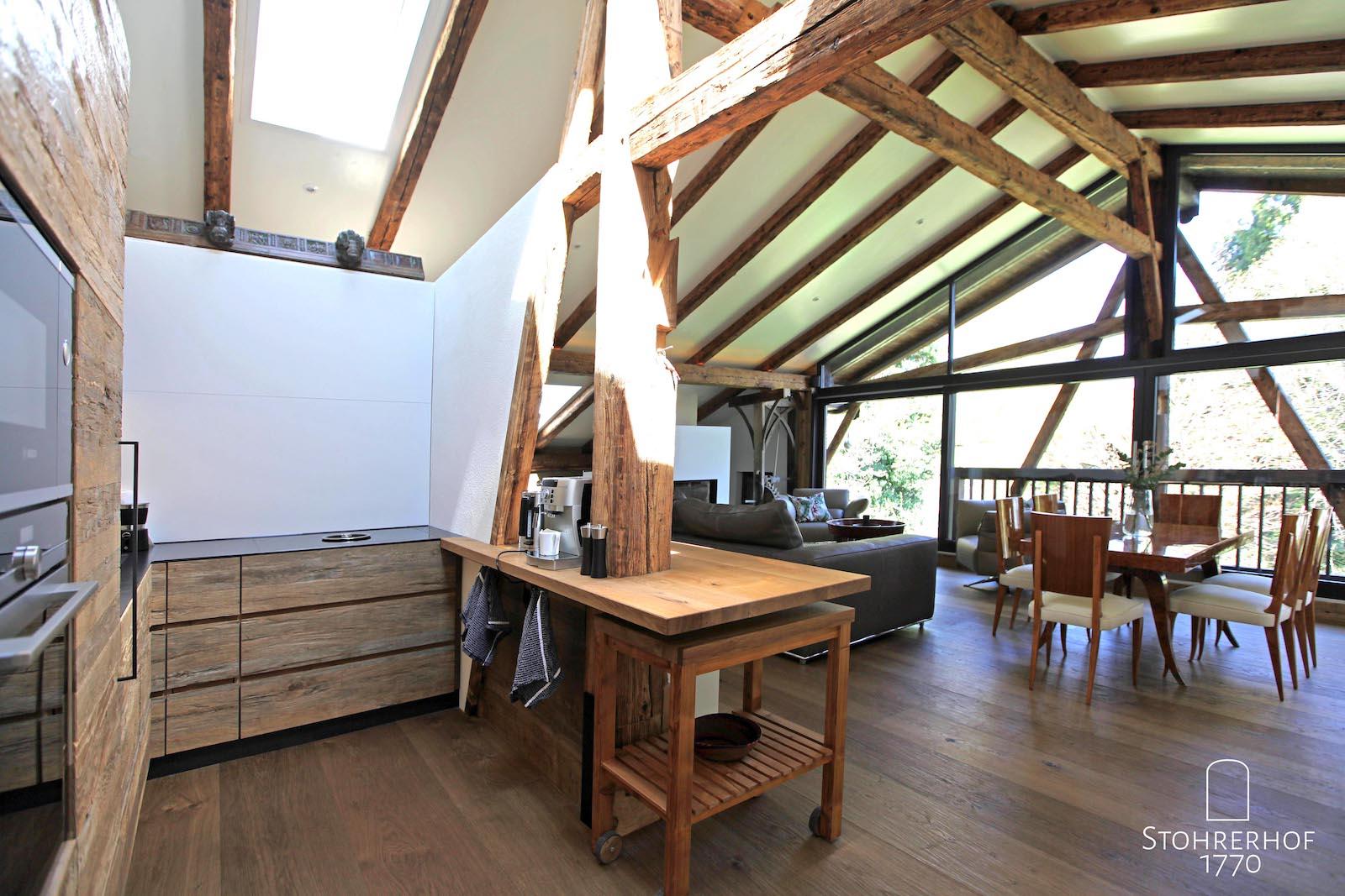 25-Penthouse-Blick-aus-Küche-mit-Herd-auf-Wohnen-mit-Esstisch-und-Sofa-K